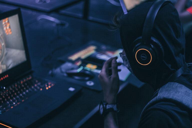 Ein Mann sitzt vor einem erleuchteten Gaming-Laptop. Er trägt ein Headset.