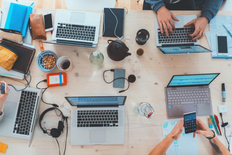 Auf einem Schreibtisch stehen 5 Laptops unterschiedlicher Marken und Größen. Dazwischen sind Smartphones, Powerbanken und Stifte sowie Essen verteilt.