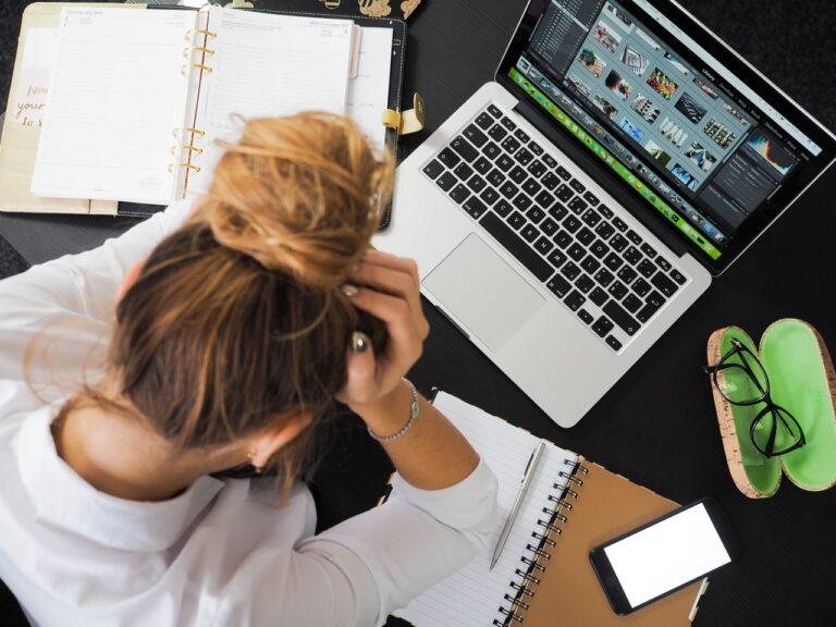 Eine Frau stützt ihren Kopf auf und sitzt vor einem Laptop. Daneben liegt eine Brille, ein Buch und ein Handy.