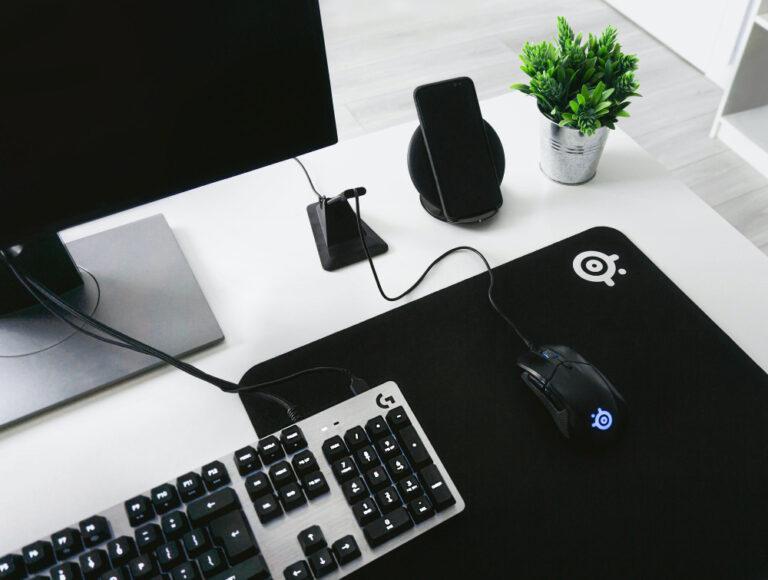 Auf einem Schreibtisch steht ein PC-Bildschirm, eine Tastatur und eine Gaming-Maus auf einem Mauspad